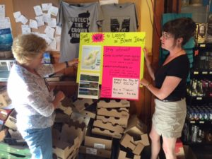 Ellen and Liz unveil the sign they've made to alert people to the perils of logging on Bowen Island